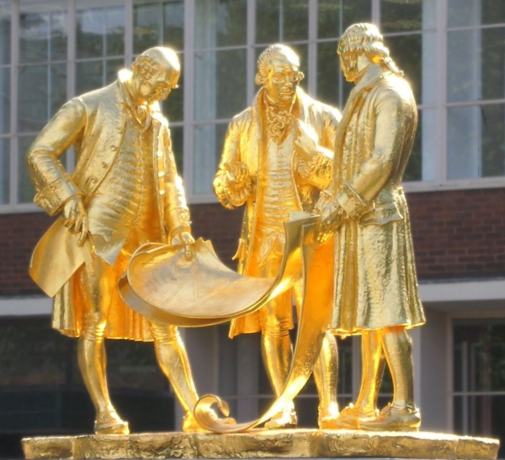 Gilded statue of Boulton, Watt and Murdoch – pictured in central Birmingham in 2006 by Oosoom and shared on English Wikipedia. This file is licensed under the Creative Commons Attribution-Share Alike 3.0 Unported license.