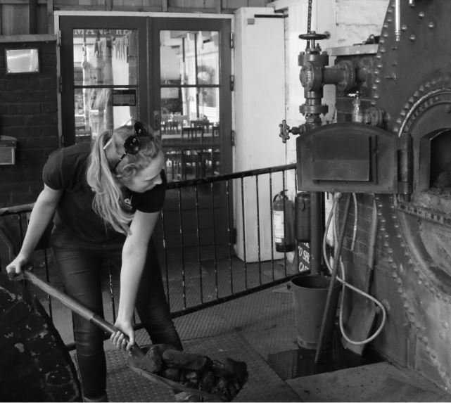 Catherine Hutchings from the Kennet and Avon Canal Trust shovelling coal into the boiler at Crofton Pumping Station.